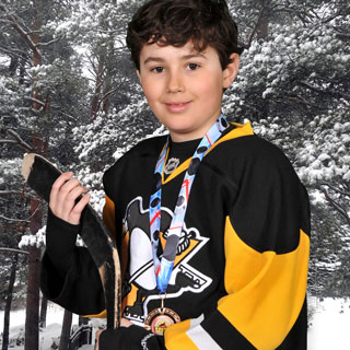 Young boy hockey player posing in front of snowy scene